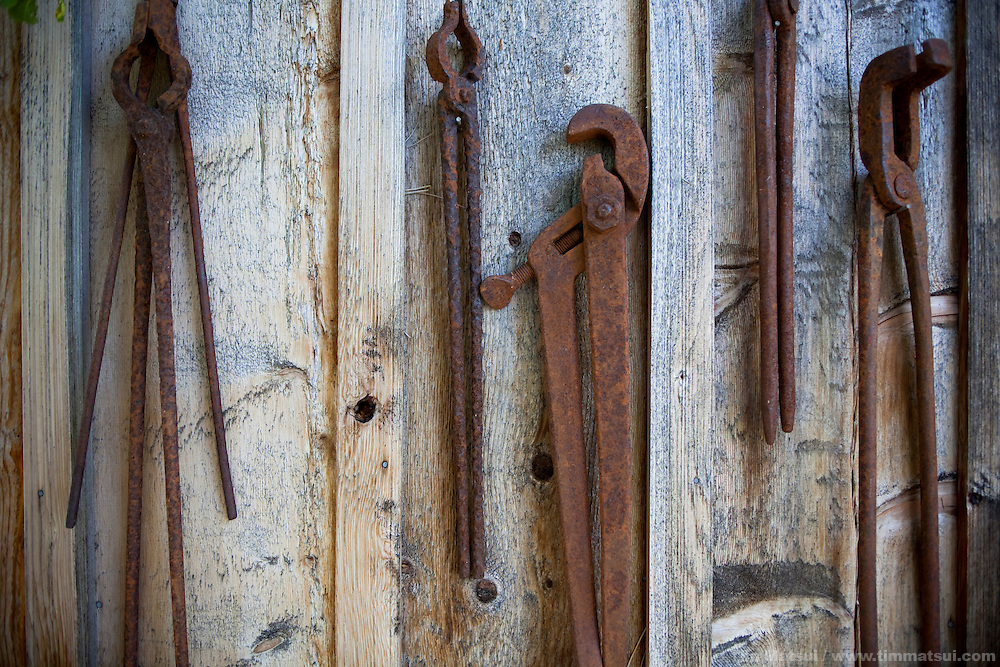 Rusted blacksmith tools hang on display on a wooden barn wall.