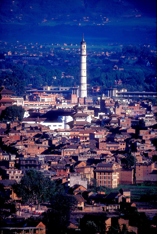 The city of Kathmandu, seen from the temple hill of Swyambhu in the early 1980s. At center are the pagoda temples and the white, royal palace in Dubar Square, plus the 203-feet-tall Dharahara Tower, originally built in 1832 as a military lookout post, but destroyed by an  earthquake in 2015. At lower left is a suspension footbridge over the Vishnumati River.