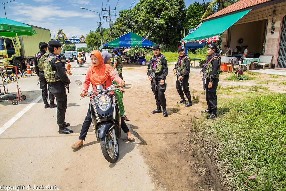"""25 OCTOBER 2012 - TAK BAI, NARATHIWAT, THAILAND: Thai women Rangers (paramilitary operating under Army command) pass  Muslim women through a checkpoint in Tak Bai, Thailand. The """"Tak Bai Incident"""" took place on Oct. 25 in Tak Bai, Narathiwat, Thailand during the Muslim insurgency in southern Thailand. On that day, a crowd gathered to protest the arrest of local residents. Police made hundreds of arrests during the protest and transported the arrested to Pattani, about two hours away, in another province. They were transported in locked trucks and more than 80 people suffocated en route. This enraged local Muslims and shocked people across Thailand. No one in the Thai army accepted responsibility for the deaths and no one was ever charged. In the past, the anniversary of the incident was marked by protests and bombings. This year it was quiet. More than 5,000 people have been killed and over 9,000 hurt in more than 11,000 incidents, or about 3.5 a day, in Thailand's three southernmost provinces and four districts of Songkhla since the insurgent violence erupted in January 2004, according to Deep South Watch, an independent research organization that monitors violence in Thailand's deep south region that borders Malaysia.   PHOTO BY JACK KURTZ"""