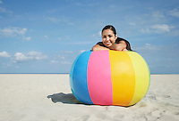 Teenage girl (16-17) sitting behind beach ball on beach portrait