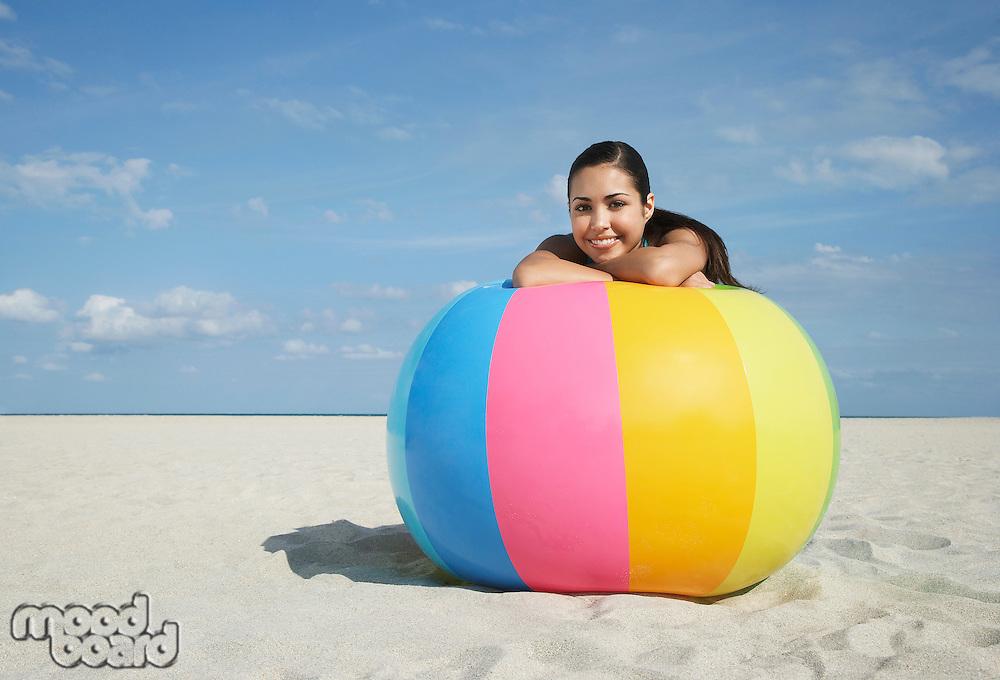 Teenage girl (16-17) sitting behind beach ball on beach portrait