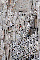 Milan, Italy, Duomo Cathedral - detail from the roof showing intricate and elaborate stonework decoration with columns, statues, gargoyles, towers,