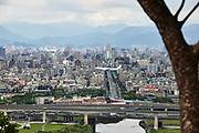 A China Airlines plane on final approach to Taipei International Airport, with the Taipei cityscape in the background. The airport, located in the Songshan district of central Taipei, is used for domestic and regional international flights.