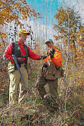 Two veteran bird hunters examine a recently bagged woodcock in Wisconsin
