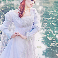 A pretty young redheaded woman wearing a fancy white wedding gown outside looks away mournfully