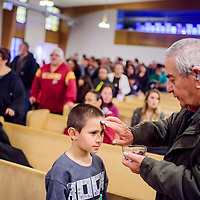 Israel Olguin receives ashes from Kenneth Lloyd, right, during the Ash Wednesday mass at Saint Francis Church in Gallup Wednesday.