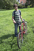 Model released image of boy holding a bike in countryside, Suffolk, England,UK