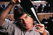 Ironhorse Vineyards, Sebastapol, California producers of sparkling and still wines.  Winemaker Forrest Taucer holds up a bottle of aging sparkling wine. MODEL RELEASED.