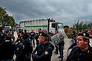 ITALY, GIUGLIANO : Riot police secure the passage of garbage lorries to the Taverna del Re dump in Giugliano on November 1, 2010. Overloaded garbage lorries were unable to reach one of the southern Italian city's two landfill sites, while local residents prevented the lorries from unloading at the other. The long-running waste issue has been blamed on a lack of local incinerators and landfill sites controlled by the local mafia, the Camorra, some of which were used for the illegal dumping of toxic waste. AFP PHOTO / ROBERTO SALOMONE