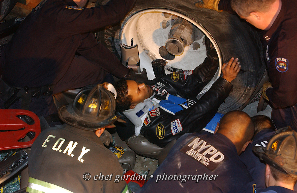 Emergency Services Personnel, New York City Police and FDNY firemen work to free a trapped driver from the rear wheels of a tractor-trailer after an accident in the northbound lanes of the Major Deegan Expressway in the Bronx, NY on Thursday, December 30, 2004.