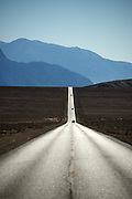 Cars are silhouetted as they drive south along Badwater Road in Death Valley National Park, Calif., on Oct. 24, 2012.