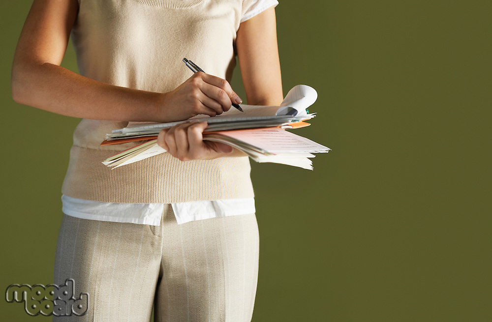 Young woman standing holding notepad writing mid section