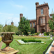 Smithsonian Castle from Enid A. Haupt Garden. The Smithsonian Castle seen from the Enid A. Haupt garden. Formally known as the Smithsonian Institution Building, the Smithsonian Castle houses the administrative headquarters fo the Smithsonian Institution as well as some a permanent exhibition titled Smithsonian Institution: America's Treasure Chest. It's distinctive architectural style stands out on the southern side of the National Mall in Washington DC. Shallow depth of field, with the focus on the urn in the foreground at left.