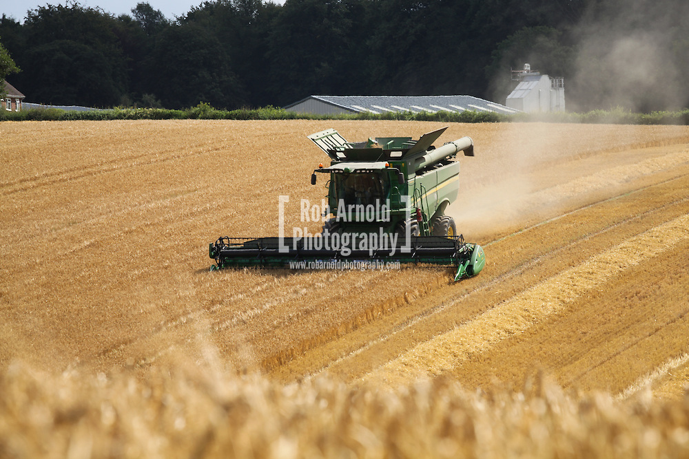 © Rob Arnold.  07/08/2014. Hampshire, UK. Barley being harvested in fields on the Malshanger estate. The barley is turned into malted barley and used in brewing. The farm's prized crop is the Black Mitcham peppermint, which is used for making tea and oil, used in food making. The oil is available direct from Summerdown Mint, but is also available from Neal's Yard in London. The tea is sold at leading retailers nationwide, including Booth's, Harvey Nichols, Partridge's & Waitrose. Photo by Rob Arnold