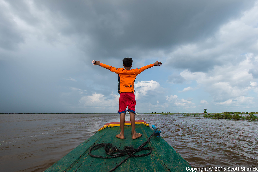 A young Cambodian boat driver looks out over the Tonle Sap from the front of his boat.