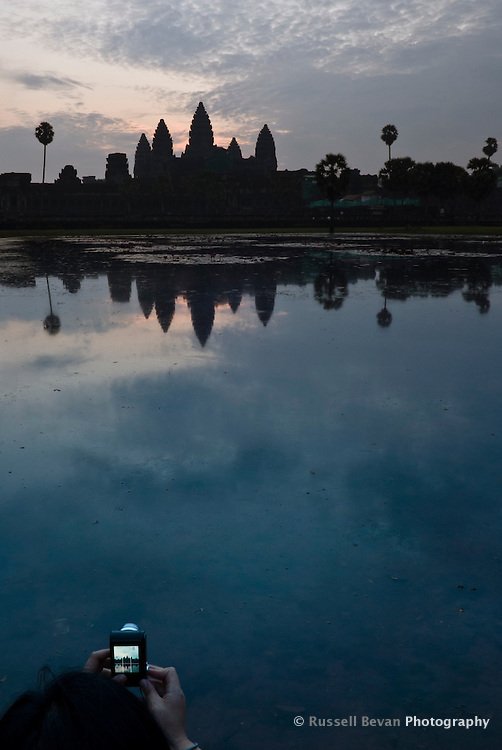 A tourist snaps a shot of sunrise at Angkor Wat Temple, Siem Reap, Cambodia