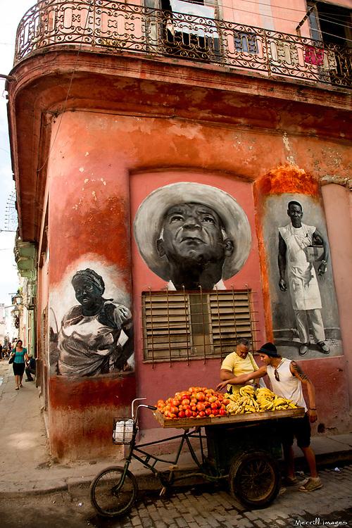 Caribbean, Cuba, Havana, woman buying tomatoes from fruit vendor near murals