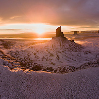 USA, Arizona, Monument Valley Navajo Tribal Park, Aerial panoramic view of winter sunrise behind snow-covered sandstone mesas in Monument Valley