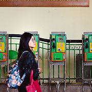 Passenger walking past public telephones on platform at Hua Lamphong train station