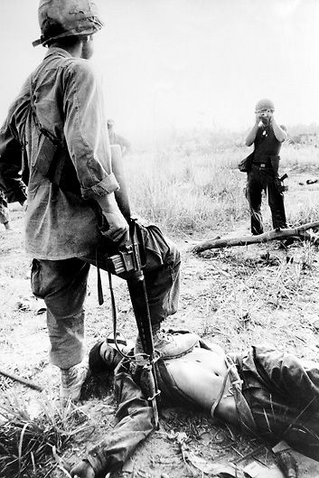 Ist Armed Cavalry soldier takes photo of US Army GI and dead Vietnamese soldier after battle in the Vietnam War