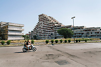 """NAPLES, ITALY - 30 JULY 2018: A view of the Vele di Scampia (English: Sails of Scampia), a large urban housing project built between 1962 and 1975 in the Scampia neighbourhood, one of the poorest and most disadvantaged in Italy, is seen here in Naples, Italy, on July 30th 2018.<br /> <br /> Thanks to Roberto Saviano's bestselling book """"Gomorrah"""" — and subsequent film and TV series — the the Vele di Scampia are known worldwide as a hotbed for drugs, prostitution and the mafia. In 2016 the city council announced an ambitious €58 million plan to tear down three of the decaying buildings and convert the fourth into offices.<br /> <br /> After the first death threats of 2006 by the Casalese clan , a cartel of the Camorra, which he denounced in his exposé and in the piazza of Casal di Principe during a demonstration in defense of legality, Roberto Saviano was put under a strict security protocol. Since 2006 Roberto Saviano has lived under police protection.<br /> <br /> Saviano's latest novel """"The Piranhas"""", which tells the story of the rise of  a paranza (or Children's gang) and it leader Nicolas, will be released in the United States on September 4th 2018.<br /> Saviano's latest novel """"The Piranhas"""", which tells the story of the rise of  a paranza (or Children's gang) and it leader Nicolas, will be released in the United States on September 4th 2018."""
