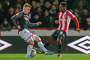 Stoke City midfielder Thibaud Verlinden (23) tackled by Brentford midfielder Joel Valencia (16) during the The FA Cup match between Brentford and Stoke City at Griffin Park, London, England on 4 January 2020.