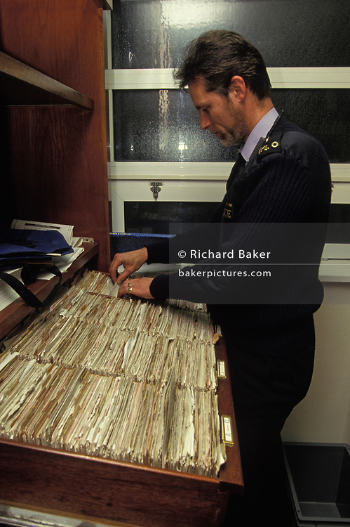 A City of London Police officer based at Bishopsgate station, flicks through a card index system during a nineties pre-digital era, on 16th June 1993, in London, England.