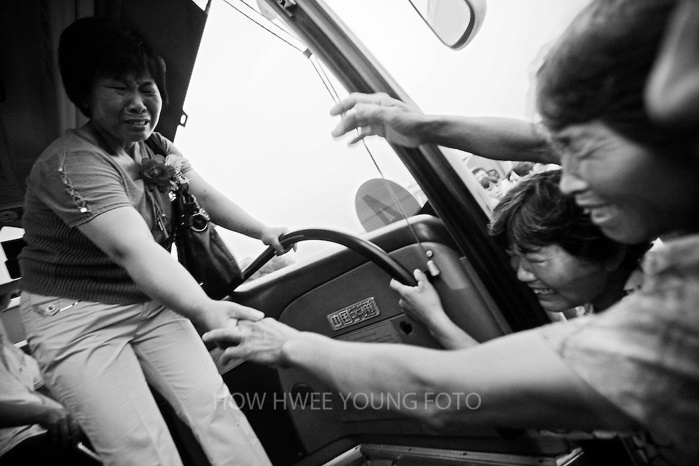 A migrant villager of Cangfang town cries as she bade farewell to her family while boarding a bus for relocation to neigbouring Hui county, more than 500 kilometers away, to make way for the colossal South-to-North Water Transfer project in Xichuan county of Henan Province in China on 29 June 2010. The South-to-North Water Transfer project, the largest known water diversion project, was conceived in 1952 to solve the country's chronic water shortages and involves creating three routes to channel 44.8 billion cu m of water from southern China to the northern areas. As part of the project's central route, affecting Henan and Hubei provinces, water from the Danjiangkou reservoir will be diverted to Beijing. The central route, which will raise the height of the Danjiangkou reservoir dam from 162 meters to 176.6 meters, requires the relocation of 330,000 people in Henan and Hubei provinces. Parts of Xichuan county, a remote, mountainous region inaccessible by railway and home to 162,000 migrants, the most anywhere, will be completely submerged by water from the Danjiangkou reservoir by 2014. The vast resettlement of affected residents in Xichuan county began in August 2009 and lasted till 2011.