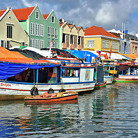 Floating Market in Punda, Eastside of Willemstad, Curaçao  <br /> This view of the Floating Market from the Queen Wilhelmina bridge makes it seem the market is conducted from the tethered boats along the Waaigat waterfront. However, behind those tarps are produce stalls brimming with fresh fruits, vegetables and fish. They are built along the colorful buildings of Shailio Caprileskade. Many Venezuelan merchants live in those small wooden boats. They also use them to transport their fresh product from their homeland 40 miles away across the Caribbean.