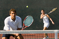 Mixed Doubles player hitting tennis ball partner standing near net