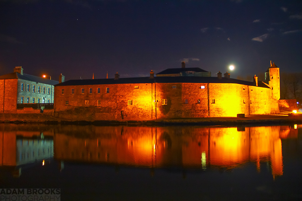 Enniskillen Castle at night with the River Erne in the foreground providing some lovely reflections. The moon looms just above the castle, with Arcturus off to the left of the night sky.