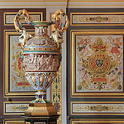 Large Sevres porcelain vase made 1832 in Renaissance style, representing the legends of Fontainebleau, such as Leonardo da Vinci with the Mona Lisa and Benvenuto Cellini sculpting Diana in front of Diane de Poitiers, in the Guard Room at the Chateau de Fontainebleau, France. In the background are the decorative painted wall panels of the Guard Room. The Palace of Fontainebleau is one of the largest French royal palaces and was begun in the early 16th century for Francois I. It was listed as a UNESCO World Heritage Site in 1981. Picture by Manuel Cohen