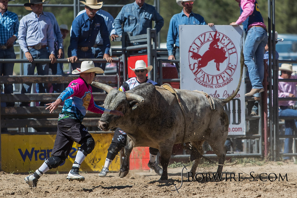 Bullfighters Cade Burns (left) and Nate Jestes come to the rescue of bull rider Garrett Uptain in the first performance of the Elizabeth Stampede on Saturday, June 2, 2018.