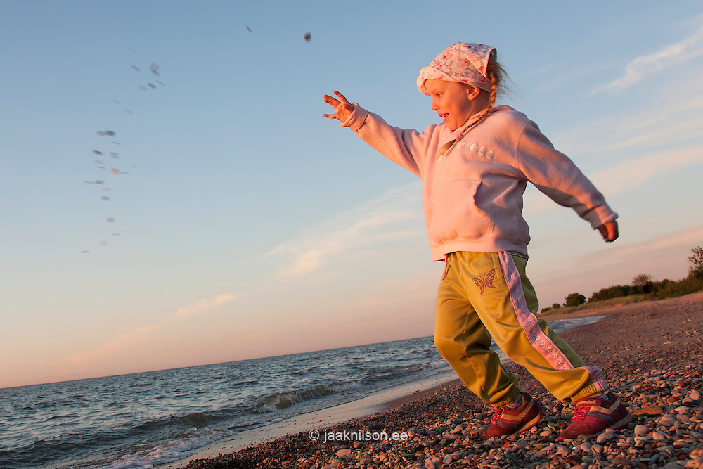 Young Kid Girl Throwing Stones into Water on Beach