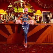 Girl in blue rubber dress and pink bowler hat at bar