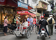 A tourist in a cyclo on a busy street in the Old Quarter, Hanoi, Vietnam, Southeast Asia