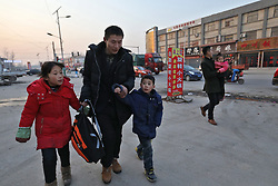 epa05830821 Chinese migrant worker Wang Pengfei (C) walks with his two children Ruiqi (L) and Yaqin (R) as he arrives in Heze City, Shandong Province, China, 22 January 2017. Wang is the migrant worker and is working in the capital city as a delivery man. He will travel to visit his family in the Shandong Province for the annual Chinese Lunar New Year or Spring Festival. This is the only time he gets to see his family each year. Wang will join millions of fellow Chinese travelers making their way back home as they pack trains, planes and buses, in what is the largest human migration in the world. The journey, known as 'Chunyun' - the annual spring migration, will involve a total of 2,98 billion trips, starting from 13 January and continuing until 21 February 2017  EPA/HOW HWEE YOUNG