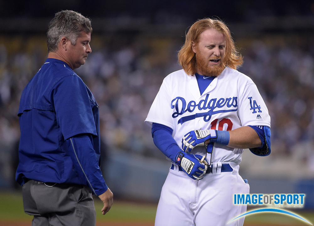 Apr 13, 2016; Los Angeles, CA, USA; Los Angeles Dodgers third baseman Justin Turner (10) reacts after being hit by a pitch as trainer Neil Rampe watches during a MLB game against the Arizona Diamondbacks at Dodger Stadium. The Dodgers defeated the Diamondbacks 3-1.