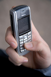 Close up of hand texting on mobile phone,