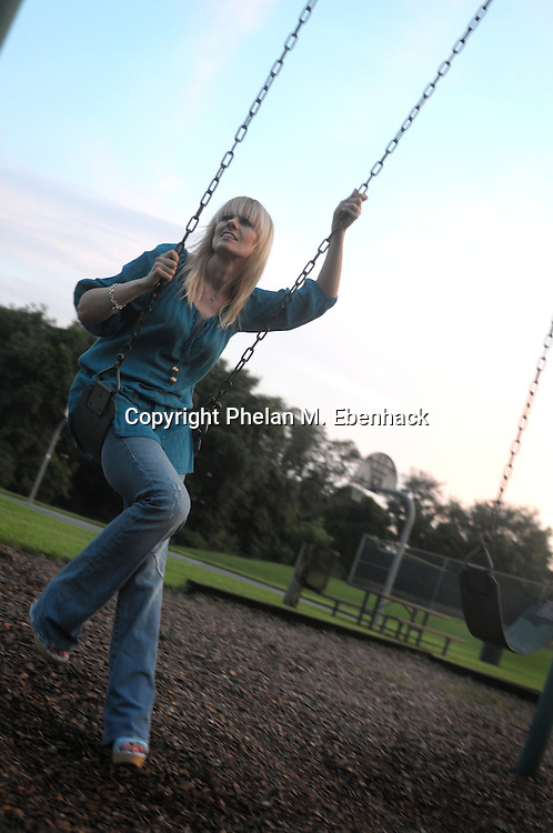 A woman sits on a swing at sunset on a playground.