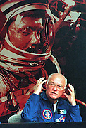 Astronaut and former Senator John Glenn describes the effects of weightlessness to the press 08 November at Kennedy Space Center, FL during a post-flight press conference.  Behind Glenn is a poster of Glenn in his Mercury 7 spacesuit.    AFP  PHOTO        Bob PEARSON/bp