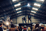 People dancing on top of speakers inside a warehouse party, Trumpkin Tek, Wales, Halloween, 29 October 2016