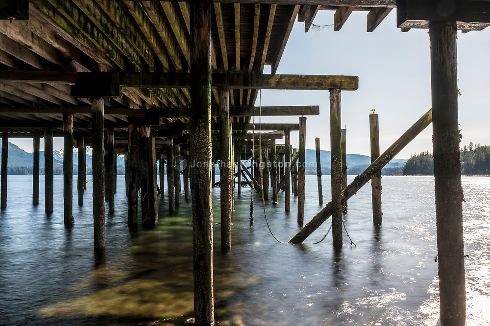 Wood pilings support a pier in Alert Bay, BC.