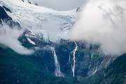 Waterfalls tumble from Rainbow Glacier in the Chilkat Range, seen from Chilkat State Park, Haines, Alaska, USA.