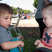 with his brand new ukulele, a three year old boy serenades a girl of the same age, at his birthday party.