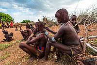Hamer tribe woman styling another woman's hair, Omo Valley, Ethiopia.