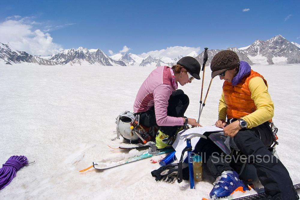 Two women ski mountaineers reading a map at Snow Lake on the Biafo glacier in the Karakoram himalaya of Pakistan