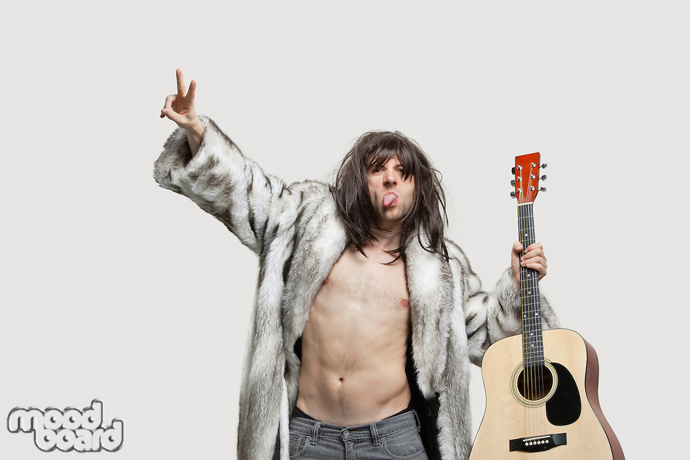 Young man in fur coat holding guitar while gesturing over gray background