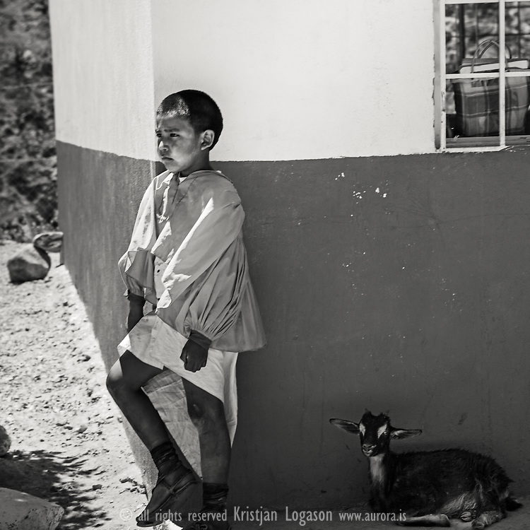 Young Tarahumara boy in the village of Munearachi leaning up against a wall in his school while a goat rests in the shadow