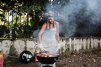 "ROME, ITALY - 3 JULY 2016: Gipsy Queens member Aninfa Hokic (31) grills meat at their food stand at the iFest, an alternative music festival  in Rome, Italy, on July 3rd 2016.<br /> <br /> The Gipsy Queens are a travelling catering business founded by Roma women in Rome.<br /> <br /> In 2015 Arci Solidarietà, an independent association for the promotion of social development, launched the ""Tavolo delle donne rom"" (Round table of Roma women) to both incentivise the process of integration of Roma in the city of Rome and to strengthen the Roma women's self-esteem in the context of a culture tied to patriarchal models. The ""Gipsy Queens"" project was founded by ten Roma women in July 2015 after an event organised together with Arci Solidarietà in the Candoni Roma camp in the Magliana, a neighbourhood in the South-West periphery of Rome, during which people were invited to dance and eat Roma cuisine. The goal of the Gipsy Queen travelling catering business is to support equal opportunities and female entrepreneurship among Roma women, who are often relegated to the roles of wives and mothers."